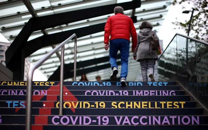People walk towards the COVID-19 vaccine and test centre at Austria Center, which has been set up as a coronavirus disease mass vaccination centre, in Vienna, Austria - LISI NIESNER / REUTERS