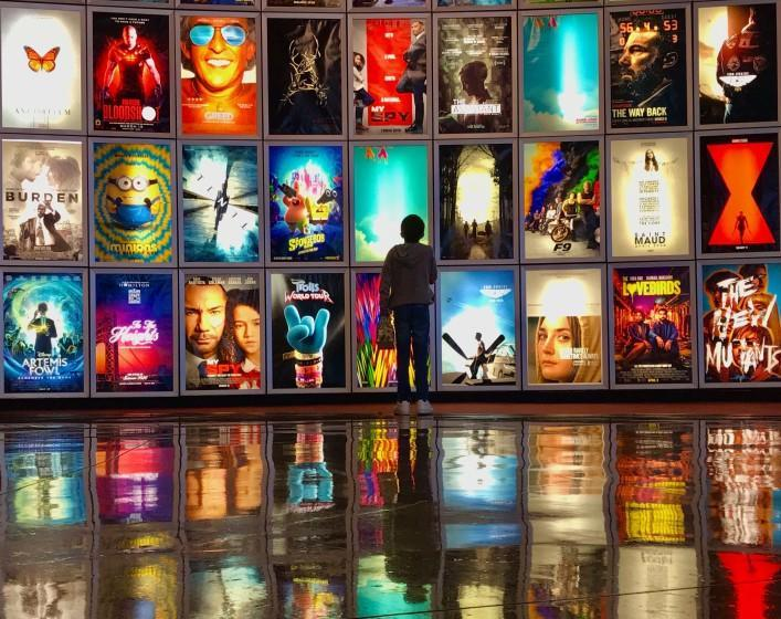 MANHATTAN BEAC CA. MARCH 12, 2020 - A child looks at movie posters inside the lobby of the Arclight movie theater In Manhattan Beach, Ca., March 12,2020. The industry is taking big losses as coronavirus spreads, with blockbusters like the latest James Bond movie and Fast and the Furios installments, being postponed indefinitely. (Jay L. Clendenin / Los Angeles Times)