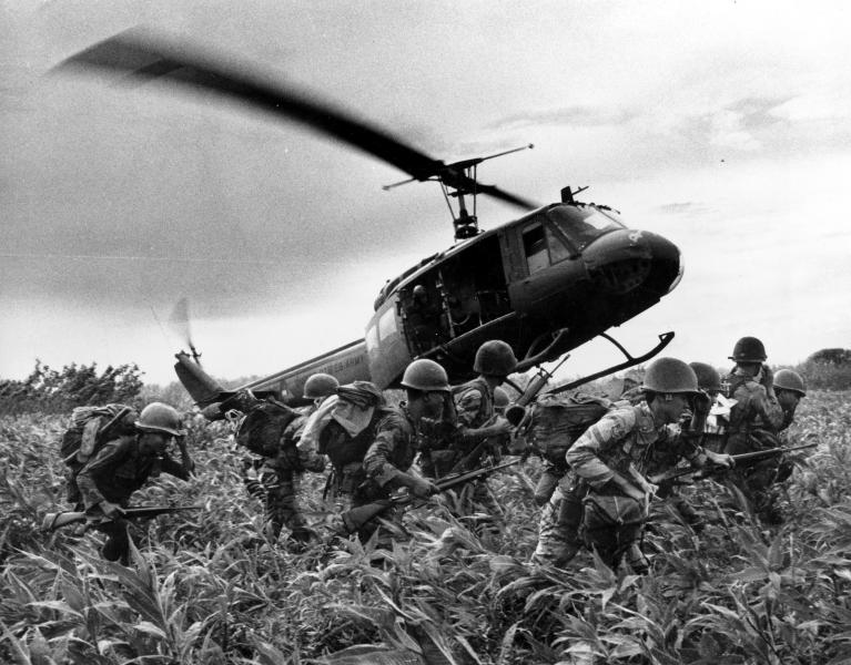 "FILE- In this June 1970 file photo, taken by Associated Press photographer Huynh Cong ""Nick"" Ut, south Vietnamese Marines rush to the point where descending U.S. Army helicopter will pick them up after a sweep east of the Cambodian town of Prey-Veng during the Vietnam War. It only took a second for Associated Press Photographer Huynh Cong ""Nick"" Ut to snap the iconic black-and-white image of Phan Thi Kim Phuc after a napalm attack in 1972, but it communicated the horrors of the Vietnam War in a way words could never describe, helping to end one of America's darkest eras. (AP Photo/Nick Ut, File)"