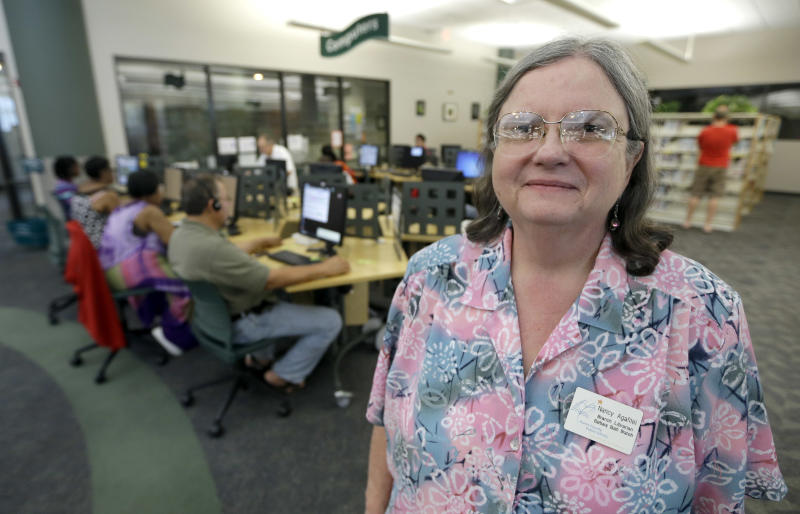 Branch librarian Nancy Agafitei poses near a computer section of the Barbara Bush Branch Library Friday, June 28, 2013, in Spring, Texas. The nation's librarians will be recruited to help people get signed up for insurance under President Barack Obama's health care overhaul. Up to 17,000 U.S. libraries will be part of the effort to get information and crucial computer time to the millions of uninsured Americans who need to get coverage under the law. The undertaking will be announced Sunday in Chicago at the annual conference of the American Library Association, according to federal officials who released the information early to The Associated Press. (AP Photo/David J. Phillip)