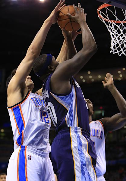 Memphis Grizzlies forward Zach Randolph, center, goes to the basket as Oklahoma City Thunder center Steven Adams (12) and Serge Ibaka, right, defend during the first quarter of an NBA basketball game on Monday, Feb. 3, 2014, in Oklahoma City. (AP Photo/Alonzo Adams)