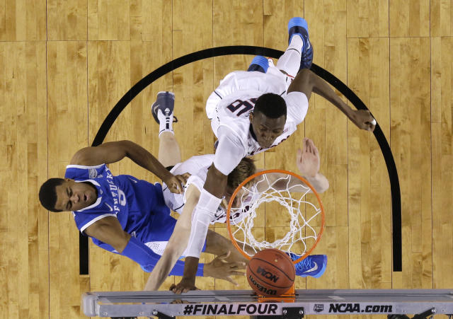 Kentucky guard Andrew Harrison, left, shoots over Connecticut's Niels Giffey, center, and Amida Brimah during the first half of the NCAA Final Four tournament college basketball championship game Monday, April 7, 2014, in Arlington, Texas. (AP Photo/David J. Phillip)