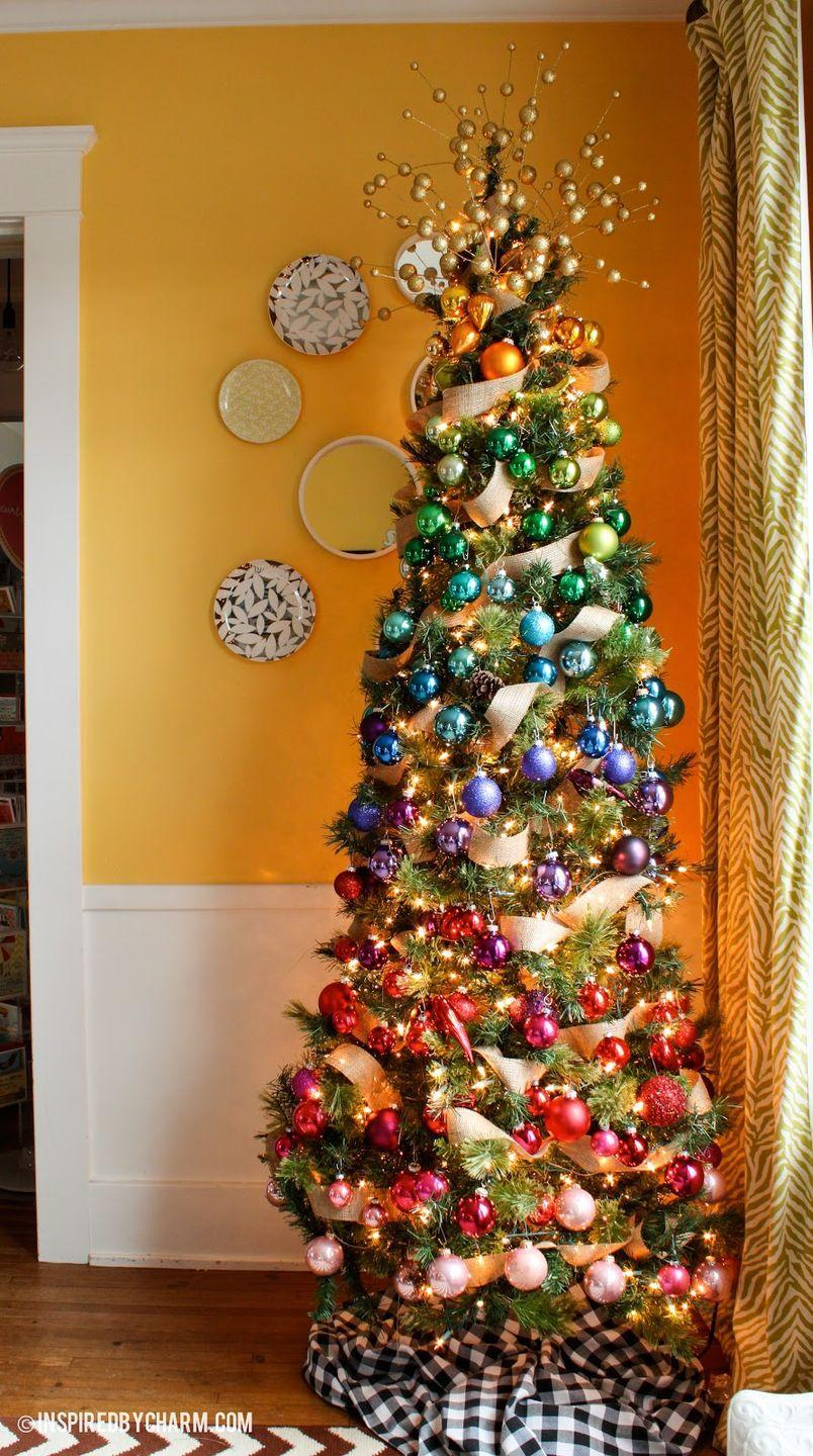 """<p>You can never go wrong with a gold ribbon—whether it's on your tree, presents, or wreath. Better yet, use the ribbon on an ombré rainbow ornament tree, like this one from <a href=""""https://inspiredbycharm.com/12-days-of-christmas-day-6-a-tree-of-a-different-color/"""" rel=""""nofollow noopener"""" target=""""_blank"""" data-ylk=""""slk:Inspired by Charm"""" class=""""link rapid-noclick-resp"""">Inspired by Charm</a>.</p>"""
