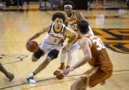 FILE - In this Feb. 6, 2021, file photo, Oklahoma State guard Cade Cunningham (2) drives past Texas forward Kai Jones (22) and Brock Cunningham (30) during the first overtime of the NCAA college basketball in Stillwater, Okla. Cunningham is a 6-foot-8 ballhandler with the ability to play on or off the ball. He's widely expected to be the No. 1 NBA draft pick after one year with the Cowboys. (AP Photo/Mitch Alcala, File)