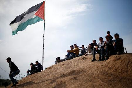 Palestinian sit near to the Israeli-Gaza border fence, ahead of the first anniversary of border protests, east of Gaza City March 29, 2019. REUTERS/Mohammed Salem
