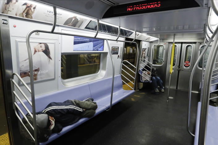 FILE - In this May 6, 2020 file photo, homeless people sleep on a train at the Coney Island Stillwell Avenue Terminal in the Brooklyn borough of New York. New York City transit officials said they're providing buses for homeless people to shelter from unseasonably frigid temperatures this weekend during newly instituted overnight subway closures. The subway system has been shutting down from 1 to 5 a.m. since Wednesday, May 6, as part of an outbreak-related plan for daily train disinfecting. (AP Photo/Frank Franklin II, File)