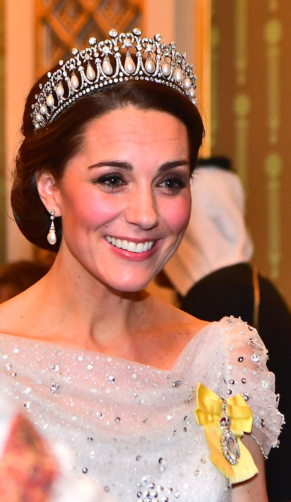 "<p>There's nothing quite like a simple chignon on the Duchess of Cambridge, particularly if it's paired with a huge pearl-and-diamond-studded tiara. This tiara, in particular, is special as it not only was a piece that <a href=""https://www.popsugar.co.uk/fashion/British-Royal-Tiaras-42087020"" class=""link rapid-noclick-resp"" rel=""nofollow noopener"" target=""_blank"" data-ylk=""slk:Princess Diana frequently wore"">Princess Diana frequently wore</a>, but it also has been in the royal family for over a century. According to <b>Town & Country</b>, the tiara seen here was made in<br> <a href=""https://www.townandcountrymag.com/society/tradition/g26533742/kate-middleton-tiara-moments/"" class=""link rapid-noclick-resp"" rel=""nofollow noopener"" target=""_blank"" data-ylk=""slk:was made in 1913 or 1914 for Queen Mary"">was made in 1913 or 1914 for Queen Mary</a> using pearls and diamonds already owned by the monarch's family, and is inspired by a tiara owned by Queen Augusta of Hesse-Cassel (another Duchess of Cambridge and one of Queen Victoria's aunts) called the Cambridge Lover's Knot. </p>"