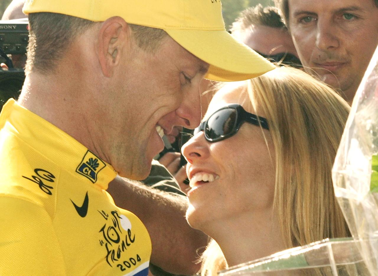 FILE - This July 25, 2004 file photo shows Lance Armstrong kissing Sheryl Crow as he celebrates his sixth straight Tour de France cycling race victory in Paris. Armstrong was stripped of his seven Tour de France titles and banned for life by cycling's governing body Monday, Oct. 22, 2012, following a report from the U.S. Anti-Doping Agency that accused him of leading a massive doping program on his teams. UCI President Pat McQuaid announced that the federation accepted the USADA's report on Armstrong and would not appeal to the Court of Arbitration for Sport. (AP Photo/Franck Prevel)