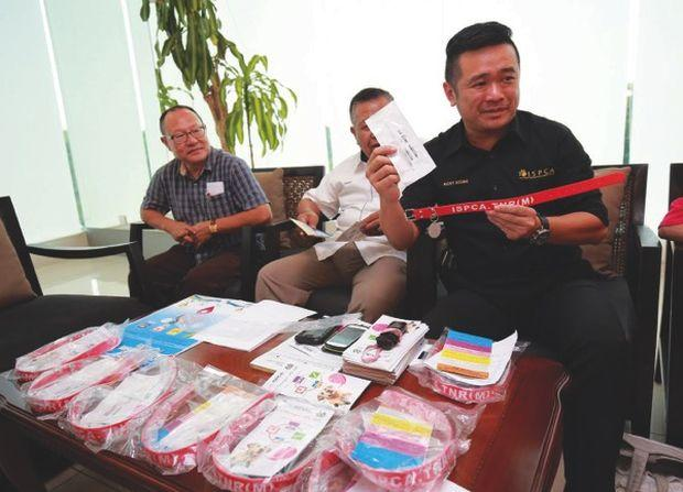 Soong (right) showing the free collar while Raduan (centre) and councillor Liew Kar Tuan look on. — Malay Mail pic