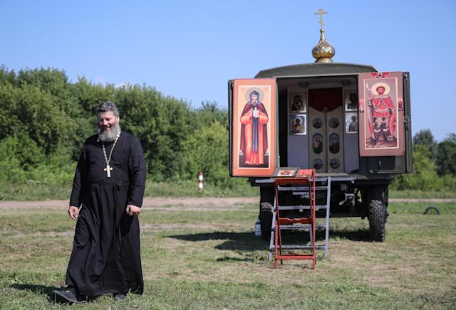 <p>A Russian Orthodox priest near a mobile chapel, during the Open Water contest between pontoon bridge units at the 2018 International Army Games on the Oka River, Vladimir Region, Russia, Aug. 3, 2018. (Photo: Sergei Bobylev/TASS via Getty Images) </p>