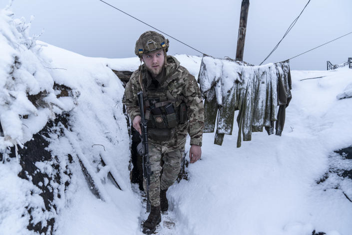 A Ukrainian serviceman walks along a snow covered trench guarding his position at the frontline near Vodiane, about 750 kilometers (468 miles) south-east of Kyiv, eastern Ukraine, Saturday, March 5, 2021. The country designated 14,000 doses of its first vaccine shipment for the military, especially those fighting Russia-backed separatists in the east. Ukrainians are becoming increasingly opposed to vaccination: an opinion poll this month by the Kyiv International Institute of Sociology found 60% of the country's people don't want to get vaccinated, up from 40% a month earlier. (AP Photo/Evgeniy Maloletka)