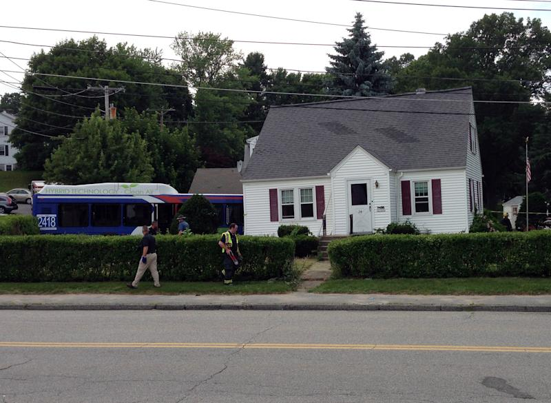 The driver of a Worcester Regional Transit Authority Bus is wheeled to a waiting ambulance Monday, June 24, 2013, after the bus crashed into a house in Auburn, Mass. Fire Capt. Eric Otterson said the driver, who was trapped for more than an hour after the 5 p.m. crash, was seriously hurt. He was taken to a hospital. (AP Photo/Worcester Telegram & Gazette, Steven H. Foskett Jr.)
