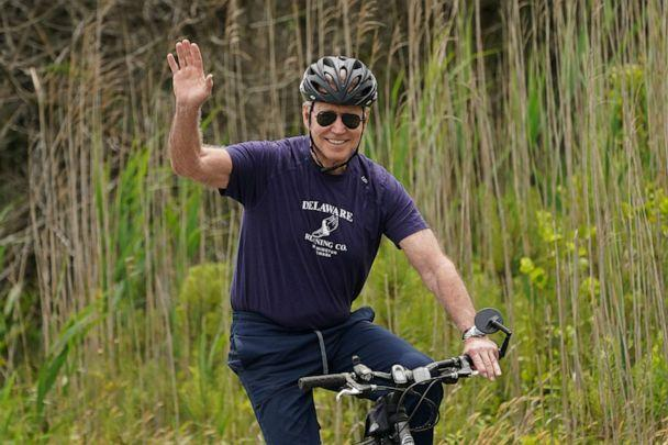 PHOTO: President Joe Biden waves from his bike while riding at Cape Henlopen State Park in Rehoboth Beach, Del., June 3, 2021. (Kevin Lamarque/Reuters)