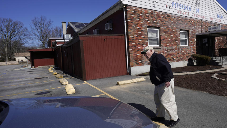Paul Guilbeault, quartermaster at Veterans of Foreign Wars Post #3260, walks through the empty parking lot of the former post, Friday, March 12, 2021, in New Bedford, Mass. Guilbeault knew the writing was on the wall for the last Veterans of Foreign Wars post in this city south of Boston when businesses across Massachusetts were ordered to close as the coronavirus pandemic took hold last March. (AP Photo/Charles Krupa)