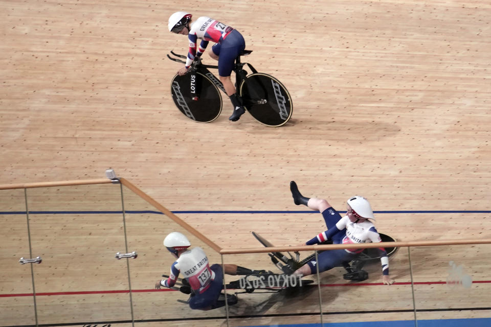Laura Kenny of Team Britain (27) watches as Neah Evans (137) and another teammate crash as they compete during the track cycling women's team pursuit at the 2020 Summer Olympics, Tuesday, Aug. 3, 2021, in Izu, Japan. (AP Photo/Christophe Ena)