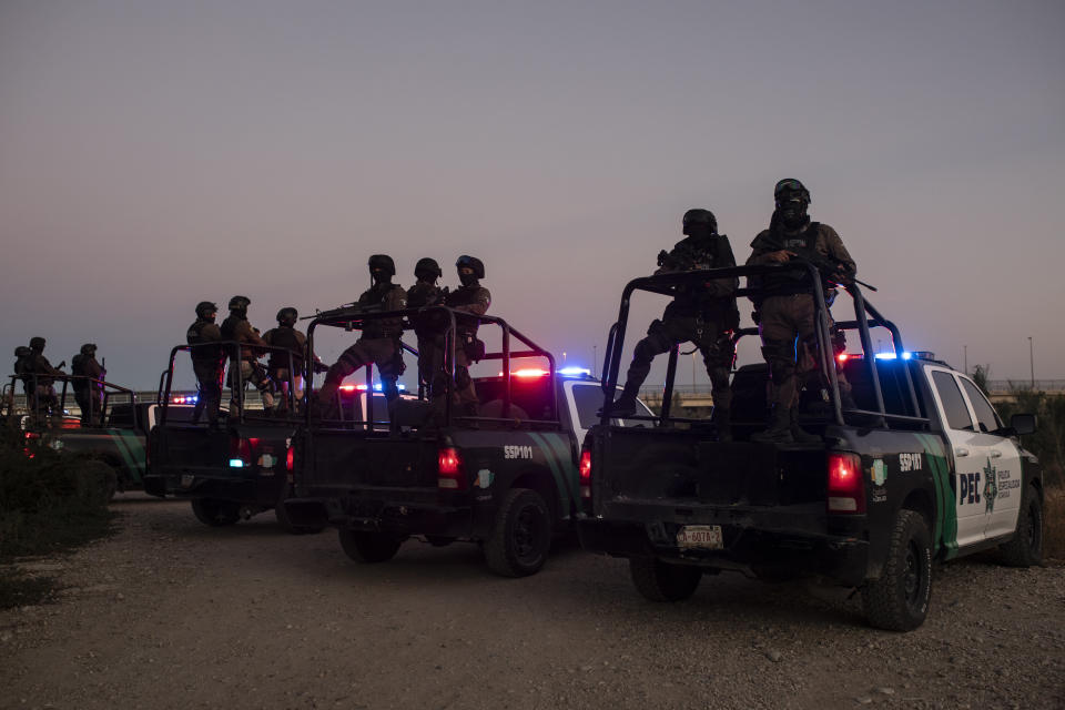 Mexican police stand guard near the Rio Grande river in Ciudad Acuna, Mexico, at dawn Thursday, Sept. 23, 2021, on the border with Del Rio, Texas. Mexico has been ramping up efforts to relieve migrant numbers at this segment of the border. (AP Photo/Felix Marquez)