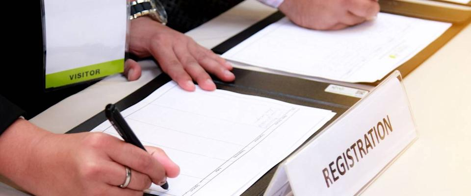 close-up of registration desk in front of conference center with Businessman Writing on the Table