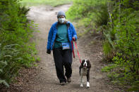 KENMORE, WA - MAY 05: Lynette Fisher-Charles and her dog Gracie, a two-year-old springer spaniel, go for a hike in Saint Edward State Park on May 5, 2020 in Kenmore, Washington. The first phase to reopen the state begins today easing some restrictions including opening some parks, that were put in place during Governor Jay Inslees Stay Home, Stay Healthy order last March to help reduce the spread of COVID-19. Kenmore, WA is located northeast of Seattle. (Photo by Karen Ducey/Getty Images)