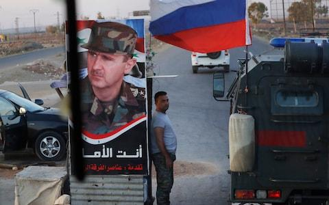 Syrian army soldier stands at a check-point as Russian military police vehicle, right, passes by near the village of Almajdiyeh, Syria, - Credit: AP