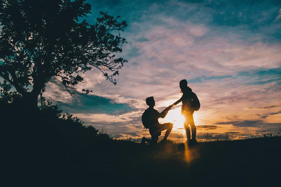 Silhouette Man Proposing Girlfriend Against Sky During Sunset