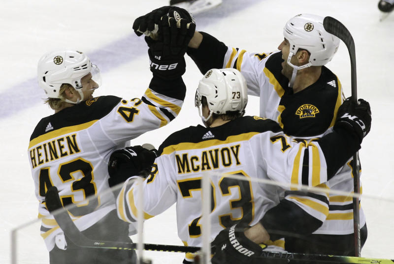 Boston Bruins' Zdeno Chara, right, celebrates with teammates Danton Heinen (43) and Charlie McAvoy (73) after scoring a goal during the second period of an NHL hockey game against the Florida Panthers, Saturday, March 23, 2019, in Sunrise, Fla. (AP Photo/Luis M. Alvarez)