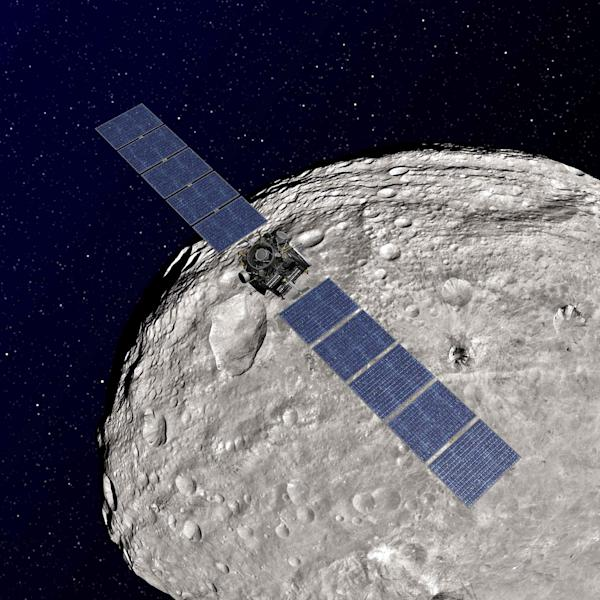 An undated artist rendering released by NASA shows the NASA Dawn spacecraft in orbit around the giant asteroid Vesta. After spending a year examining Vesta, Dawn is poised to depart and head to another asteroid, Ceres, where it will arrive in 2015.(AP Photo/NASA)