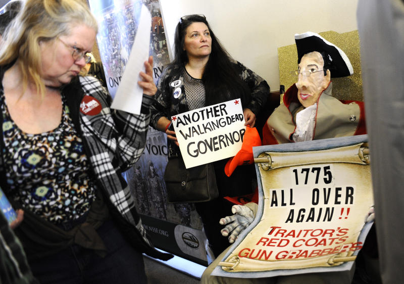 """Claudette Bleidner, center, of Southbury, Conn., stands next to a caricature  she made of Gov. Dannel P. Malloy dressed as a Redcoat soldier,  as a woman reads information of upcoming gun legislation during a """"lobby day"""" held by the National Rifle Association and and other gun rights groups at the Legislative Office Building in Hartford, Conn., Monday, March 11, 2013. Both sides of the gun control issue are increasing pressure on Connecticut lawmakers, who are close to voting on changes to state law stemming from the deadly shooting at Sandy Hook Elementary School in Newtown. (AP Photo/Jessica Hill)"""