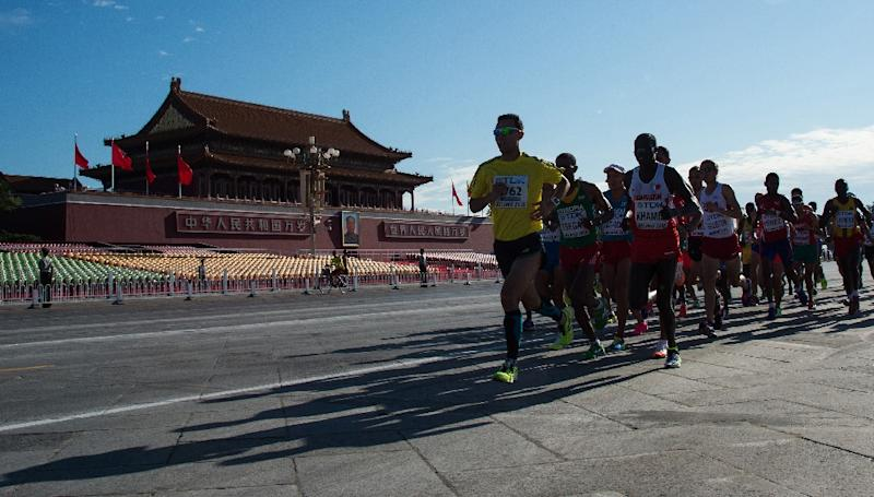 Athletes run through Tiananmen Square during the men's marathon event, at the IAAF World Championships in Beijing, on August 22, 2015 (AFP Photo/Johannes Eisele)
