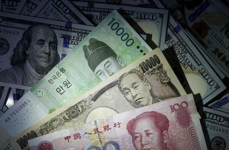 South Korean won, Chinese yuan and Japanese yen notes are seen on U.S. 100 dollar notes in this picture illustration