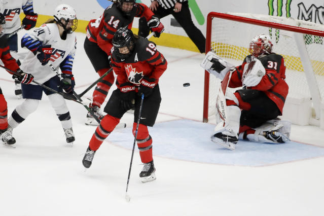 Canada goaltender Genevieve Lacasse, right, fails to stop the puck on the game-winning goal by United States' Megan Bozek during overtime in a Rivalry Series hockey game in Anaheim, Calif., Saturday, Feb. 8, 2020. The United States won 4-3 and won the series. (AP Photo/Chris Carlson)