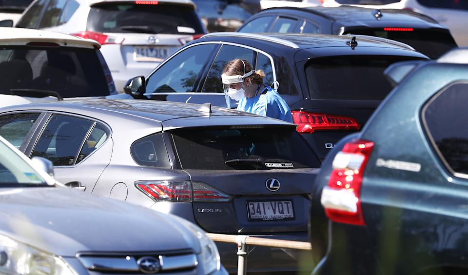 People are seen at a Covid Testing Centre at Indooroopilly High School Brisbane , Sunday, August 1, 2021. Queensland has gone into a snap three-day lockdown after six locally-acquired cases of COVID-19, reported on Saturday, were linked to an Indooroopilly High School student. (AAP Image/Jason O'Brien) NO ARCHIVING