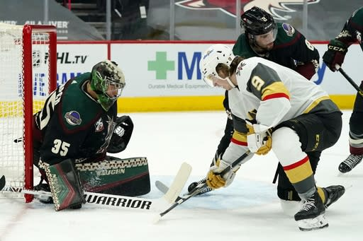 Arizona Coyotes goaltender Darcy Kuemper (35) makes a save on a shot by Vegas Golden Knights center Cody Glass (9) as Coyotes center Nick Schmaltz (8) defends during the second period of an NHL hockey game Friday, Jan. 22, 2021, in Glendale, Ariz. (AP Photo/Ross D. Franklin)