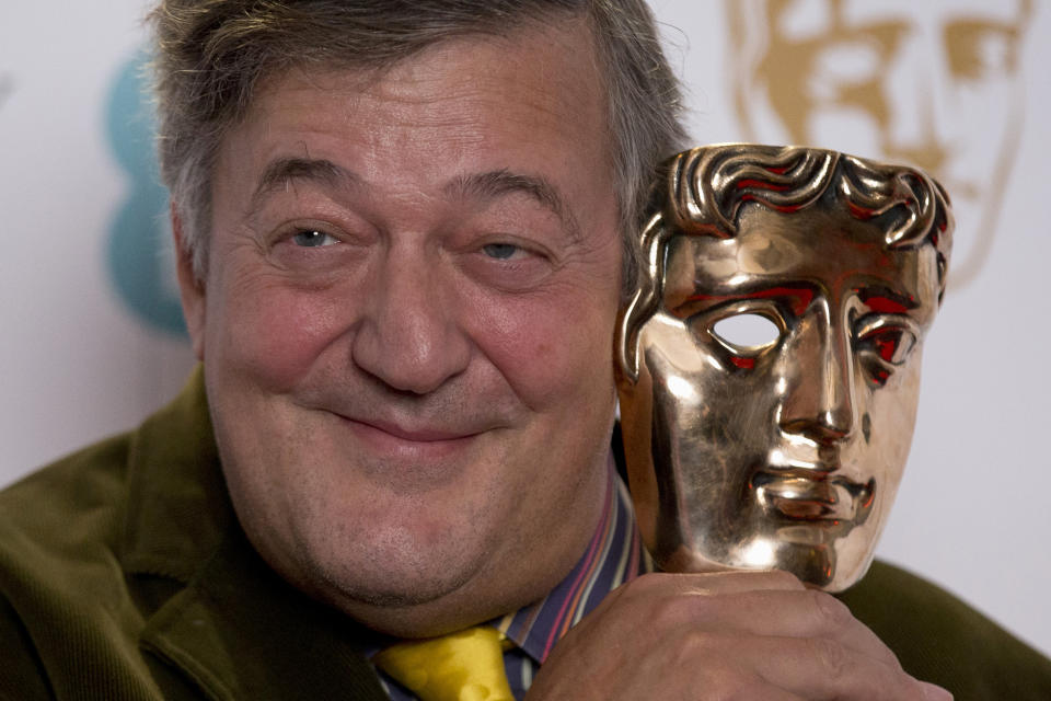 British comedian and actor Stephen Fry poses for photographs with a BAFTA (British Academy of Film and Television Arts) statuette, 2015. (AP Photo/Matt Dunham)