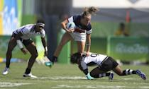 <p>Kathryn Johnson of the USA avoids a tackle by Ana Maria Roqica of Fiji during a 12-7 loss. (Reuters) </p>
