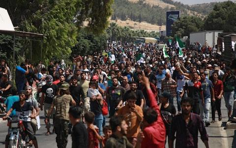 Syrians from the country's northern countryside demonstrate by the Bab al-Hawa crossing between Turkey and Syria's northwestern Idlib province  - Credit: AFP