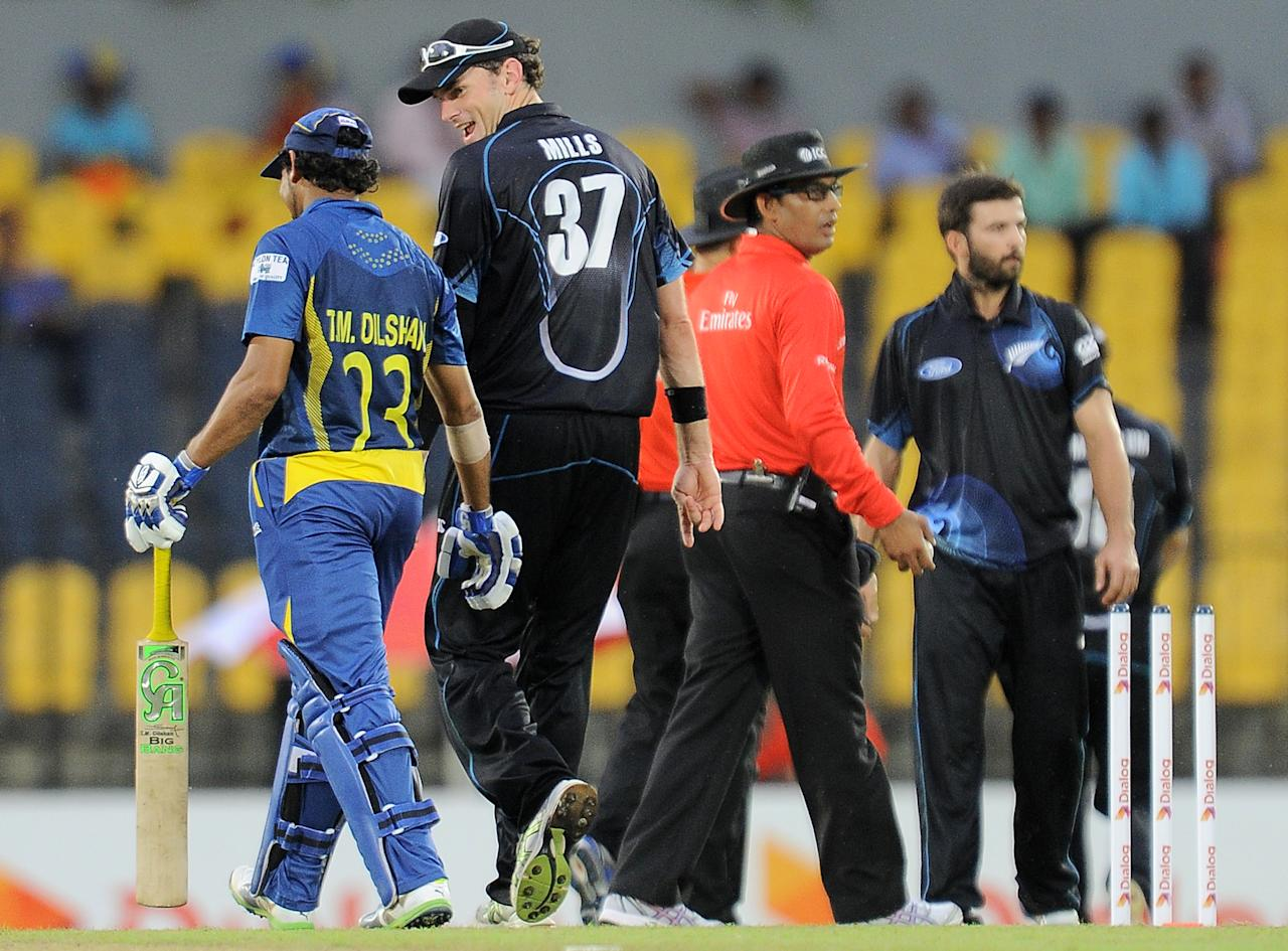 New Zealand captain Kyle Mills (2L) and Sri Lankan cricketer Tillakaratne Dilshan (L) walk back to the pavilion after rain stopped play during the second One Day International (ODI) cricket match between Sri Lanka and New Zealand at the Suriyawewa Mahinda Rajapakse International Cricket Stadium in the southern district of Hambantota on November 12, 2013. AFP PHOTO/ LAKRUWAN WANNIARACHCHI        (Photo credit should read LAKRUWAN WANNIARACHCHI/AFP/Getty Images)