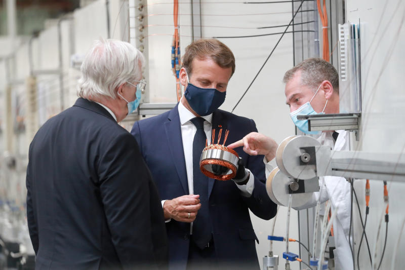 French President Emmanuel Macron, center, wearing a protective face mask, visits a factory of manufacturer Valeo in Etaples, , northern France, Tuesday May 26, 2020. Emmanuel Macron announced a 8 billion euro ($8.8 billion) plan Tuesday to save the country's car industry from huge losses wrought by virus lockdowns, including a big boost for electric vehicles. The plan includes government subsidies for car buyers and longer-term investment in innovative technology, especially in battery-powered cars. (Ludovic Marin, Pool via AP)