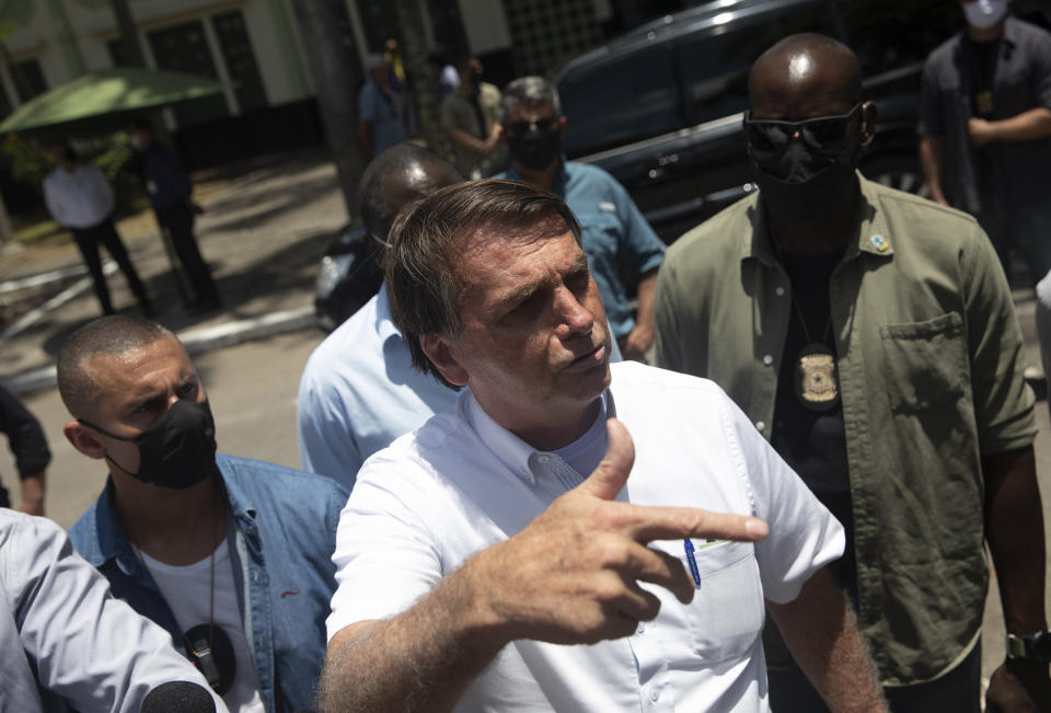 """Brazil's President Jair Bolsonaro talks with the media outside a polling station after voting during the run-off municipal elections in Rio de Janeiro, Brazil, Sunday, Nov. 29, 2020. Bolsonaro, who sometimes has embraced the label """"Trump of the Tropics,"""" said Sunday he'll wait a little longer before recognizing the U.S. election victory of Joe Biden, while also echoing President Donald Trump's allegations of irregularities in the U.S. vote. (AP Photo/Silvia Izquierdo)"""