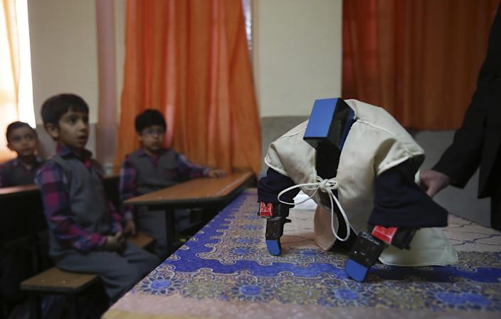 """In this picture taken on Monday, Feb. 24, 2014, Veldan, a humanoid praying robot which is built by Iranian schoolteacher Akbar Rezaie, performs morning prayer in front of Alborz elementary school boys in the city of Varamin some 21 miles (35 kilometers) south of the capital Tehran, Iran. Rezaei who has built a robot to show to children how to execute daily prayers, has innovated an amusing way of encouraging young children to say their daily prayers by using the science of robotics. Out of personal interest and unrelated to his field of study, Akbar Rezaei attended private robotics classes and acquired the skill of assembling and developing customized humanoid robots. He built the robot at home with basic tools and gave it the designation """"Veldan"""", a term mentioned in Quran meaning: """"Youth of Heaven"""". By applying some mechanical modifications such as adding up two extra engines Akbar Rezaei managed to let the robot perform praying movements, such as prostration, more easily. (AP Photo/Vahid Salemi)"""