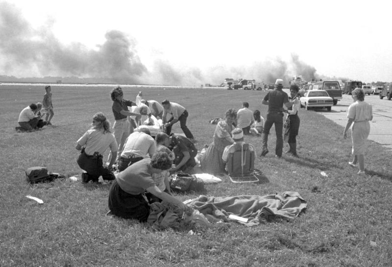 FILE - In this July 19, 1989 file photo emergency workers treat injured passengers from United Airlines Flight 232 after after the plane crash landed and cartwheeled down the runway in Sioux City, Iowa. Through through the efforts of the flight crew and emergency personnel on the ground, 184 of the 296 passengers survived. (Gary Anderaon/The Sioux City Journal, File)