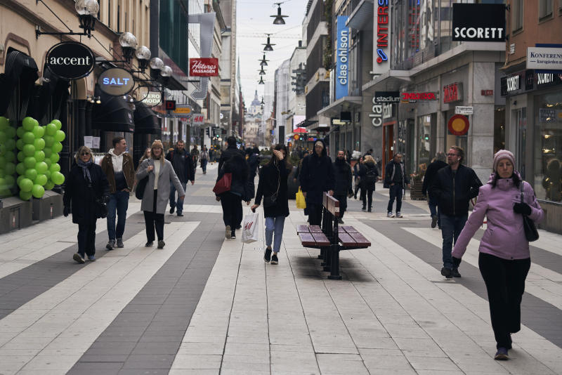 People walk along the main pedestrian shopping street in Stockholm, Wednesday, March 25, 2020. The streets of Sweden's capital are quiet but not deserted. Sweden has some of the most relaxed measures in Europe in the fight against the coronavirus outbreak. So far, only gatherings of over 500 people are banned and elementary and middle schools remain open. The new coronavirus causes mild or moderate symptoms for most people, but for some, especially older adults and people with existing health problems, it can cause more severe illness or death. (AP Photo/David Keyton)