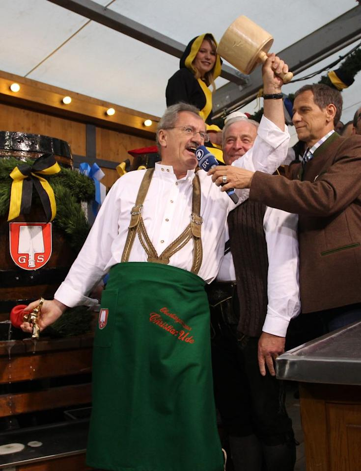 Munich mayor Christian Ude taps the first barrel of beer with the traditional 'O'zapft is!' (It's tapped!) to start the Oktoberfest 2012 beer festival at Theresienwieseat on September 22, 2012 in Munich, Germany.