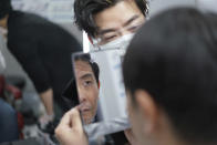 Yoshihiro Kamichi, a 44-year-old office worker, checks his face in a mirror as he receives makeup and gets his hair done by a makeup artist at Ikemen-Works, a makeup salon for men, in Tokyo Wednesday, Feb. 3, 2021. The coronavirus pandemic has been pushing businesses to the edge in Japan, but some in the men's beauty industry have seen an unexpected expansion in their customer base. Japanese businessmen in their 40s, 50s and 60s who had little interest in cosmetics before the pandemic are now buying makeup. (AP Photo/Eugene Hoshiko)