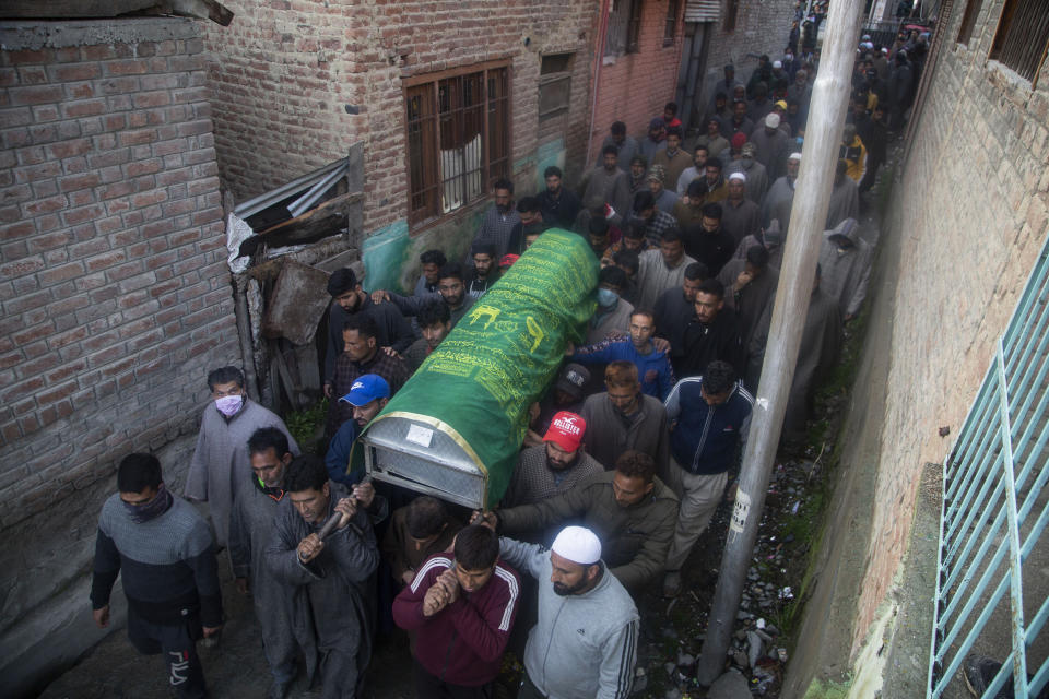 Kashmiri villagers carry the coffin of elected official Riyaz Ahmad in Sopore, 55 kilometers (34 miles) north of Srinagar, Indian controlled Kashmir, Monday, March. 29, 2021. Gunmen killed an elected official of India's ruling party and a policeman in disputed Kashmir on Monday, police said. Police blamed anti-India militants for the attack. None of the rebel groups that have been fighting against Indian rule since 1989 immediately claimed responsibility for the attack. (AP Photo/Mukhtar Khan).