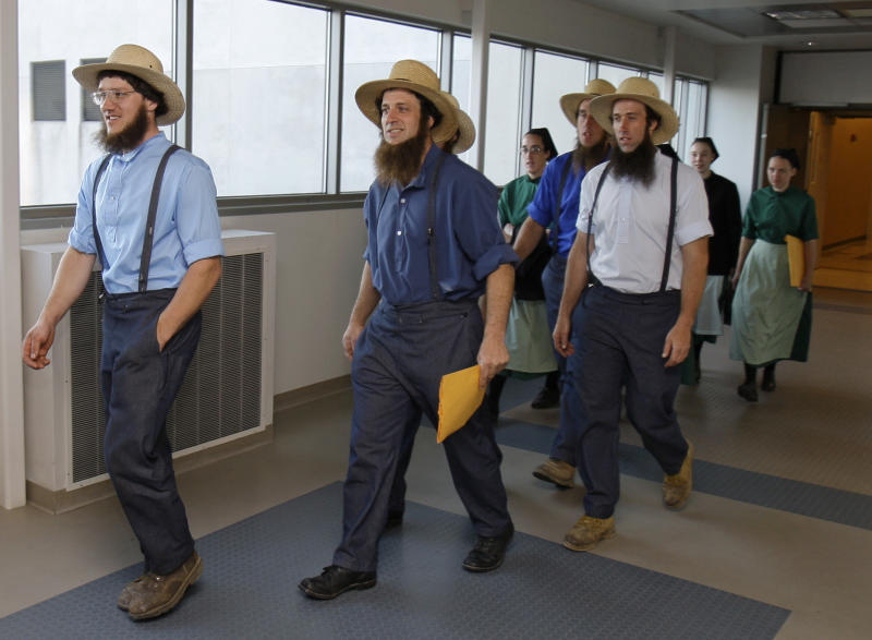 Members of the Amish community leave the U.S. Federal Courthouse Thursday, April 19, 2012, in Cleveland. Sixteen men and women have pleaded not guilty in beard- and hair-cutting attacks against fellow Amish in Ohio. A feud over church discipline allegedly led to the attacks, in which the beards and hair of men and hair of women were cut. (AP Photo/Tony Dejak)