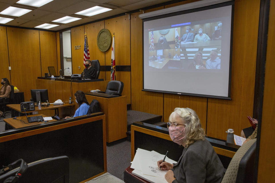 Gay Hardwick with her spouse Robert Hardwick are projected in the fourth quadrant on the projection screen behind a courtroom sketch artist, during the second day of victim impact statements with Joseph James DeAngelo present, second quadrant, at the Gordon D. Schaber Sacramento County Courthouse on Wednesday, Aug. 19, 2020, in Sacramento, Calif. Victims of California serial killer and rapist, DeAngelo want him in a maximum security prison far, far away if he can't spend the rest of his life on death row. But they may not hold much sway over where or how the 74-year-old former police officer is imprisoned once he is sentenced on Friday, Aug. 21. (Santiago Mejia/San Francisco Chronicle via AP, Pool)