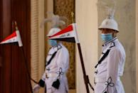 Iraqi honour guard hold national flags ahead of a regional summit in the capital Baghdad (AFP/Ludovic MARIN)