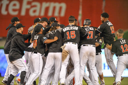 Miami Marlins celebrate after Miguel Rojas hits an RBI single in the 17th inning of a baseball game against the Chicago Cubs, in Miami Saturday March 31, 2018. Marlins won 2-1. (AP Photo/Gaston De Cardenas)