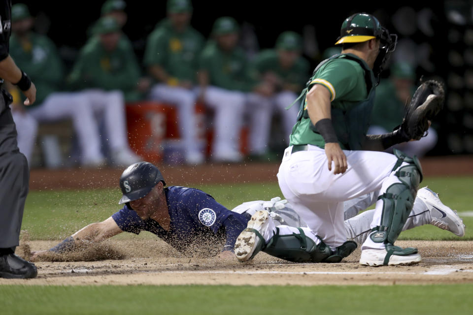Seattle Mariners' Jake Bauers slides home safe on a throwing error by Paul Blackburn as Oakland Athletics' Yan Gomes applies the tag during the second inning of a baseball game in Oakland, Calif., Tuesday, Sept. 21, 2021. (AP Photo/Jed Jacobsohn)