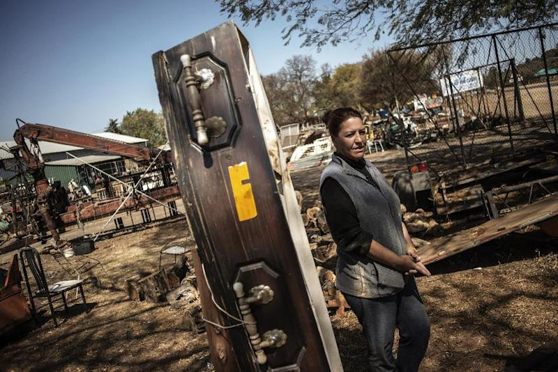 Scrapyard manager Rita Gathino stands by a coffin displayed to scare away thieves, near the main gate of her property in Cullinan, South Africa, on August 27, 2014 (AFP Photo/Gianluigi Guercia)